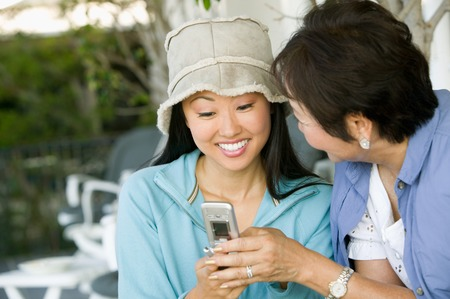 woman dialing phone number: Mother and Smiling Daughter Using Cell Phone