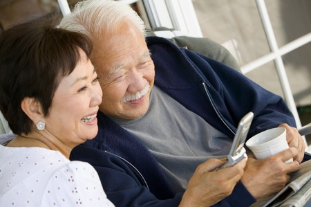 male senior adult: Couple Using Cell Phone Together LANG_EVOIMAGES