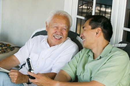 early 60s: Father and Son Laughing and Using Cell Phone