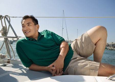 early 30s: Man Relaxing on Sailboat