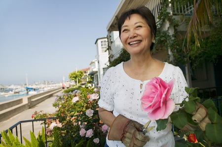 succeeding: Smiling Woman Pruning Her Roses