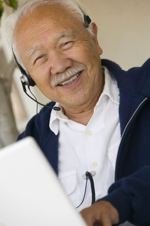Man Using Headset and Laptop Stock Photo - 5412322