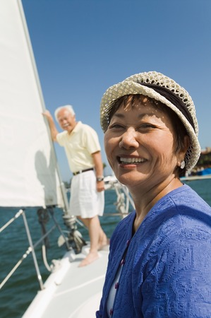 early fifties: Smiling Woman and Husband on Sailboat LANG_EVOIMAGES