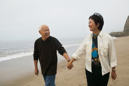 mature women only: Couple Holding Hands and Walking on Beach LANG_EVOIMAGES