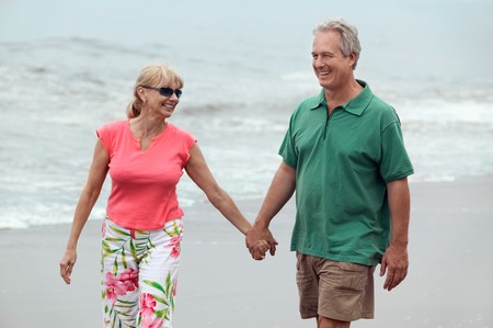 late forties: Couple Walking Hand in Hand on Beach LANG_EVOIMAGES