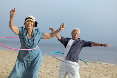vacationer: Middle-Aged Couple Hula Hooping