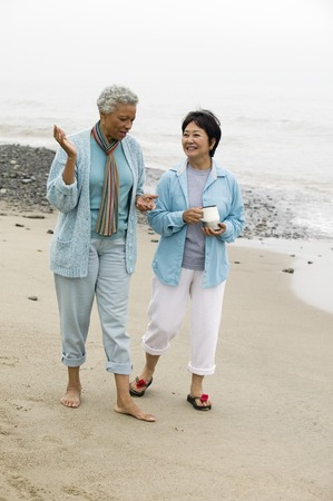 the ageing process: Two middle-aged women talking on beach LANG_EVOIMAGES