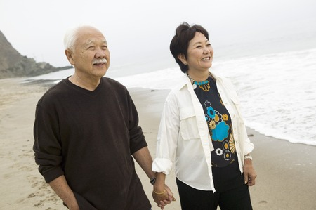 the ageing process: Senior couple on beach holding hands