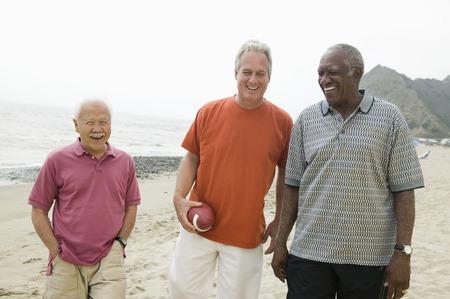 the ageing process: Three senior men walking on beach