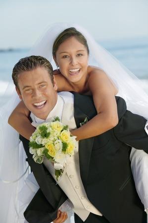 Groom Giving Bride a Piggyback Ride Stock Photo - 5412427