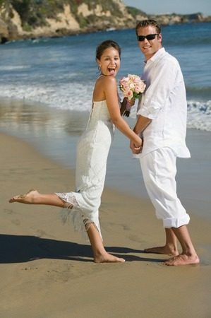 wedding customs: Excited Bride and Groom on Beach LANG_EVOIMAGES