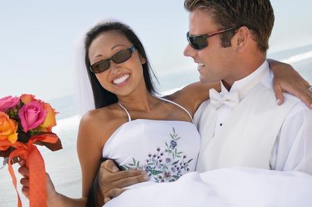 ビーチに運ぶ花嫁を新郎します。