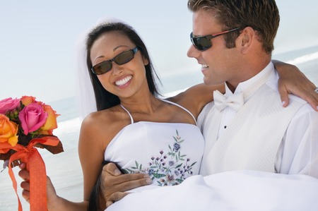 interracial marriage: Groom Bride Carrying on Beach