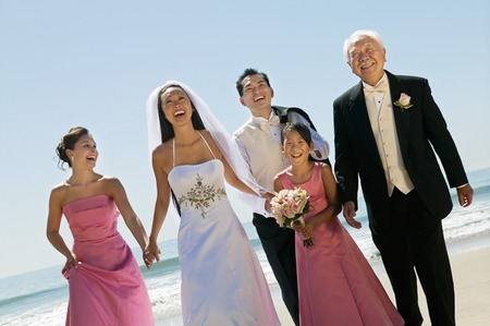 bridal gown: Happy Bride and Groom With Family on Beach LANG_EVOIMAGES