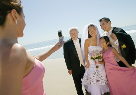 beach wedding: Bridesmaid Taking Picture of Newlyweds and Family