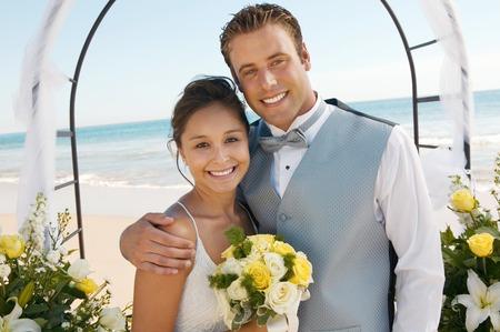 mariage mixte: Bride and Groom Sous Archway sur la plage