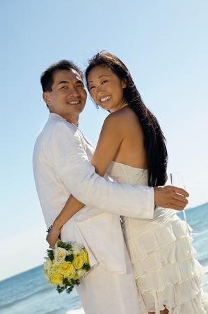 bridegrooms: Bride and Groom Embaracing on Beach LANG_EVOIMAGES
