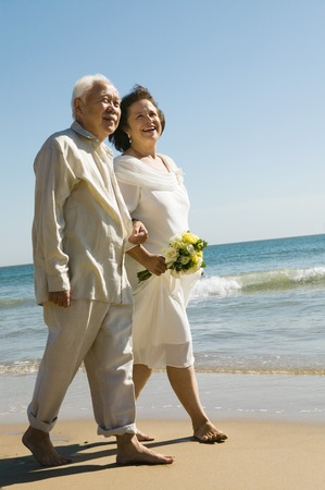 racially diverse: Senior Newlyweds Walking Along Beach LANG_EVOIMAGES
