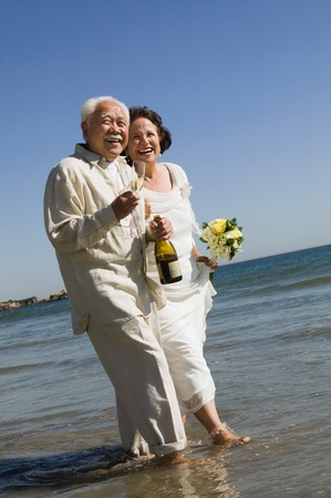 interracial relationships: Senior Newlyweds Walking in Ocean