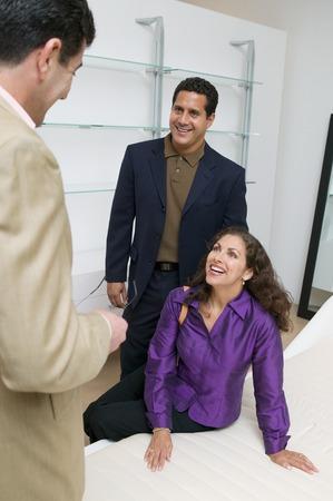 sales rep: Couple Examining Mattress With Salesman