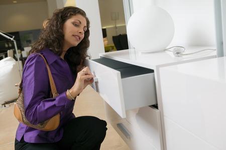 furniture store: Woman Examining White Dresser