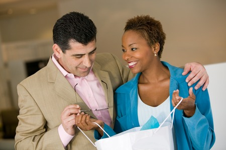 Woman Showing Man Purchases in Shopping Bag Stock Photo - 5419849