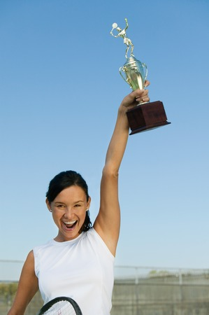 victorious: Tennis Player Holding Trophy Aloft