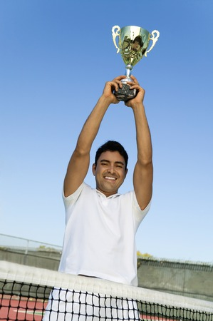 boastful: Tennis Player Holding Trophy Over Head