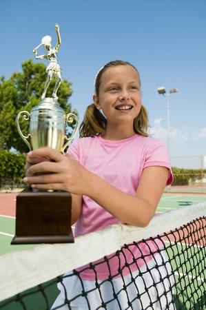 succeeding: Girl at Tennis Net Holding Trophy
