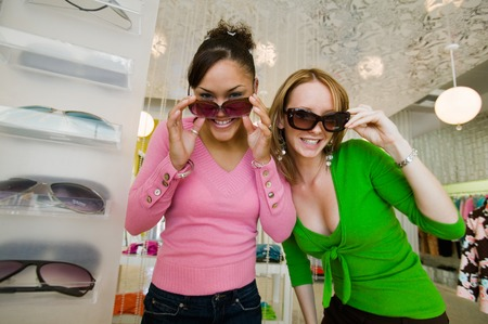 only young adults: Girls Trying on Sunglasses in Boutique