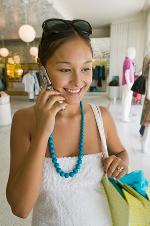 Girl Holding Using Cell Phone While Shopping Stock Photo - 5419960