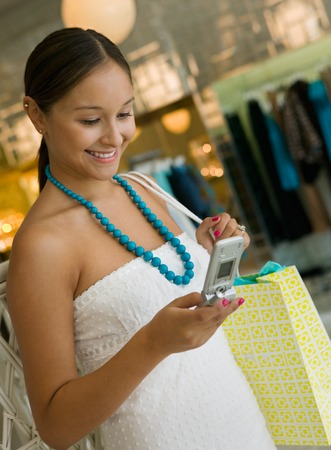teenaged: Woman Checking Cell Phone While Shopping