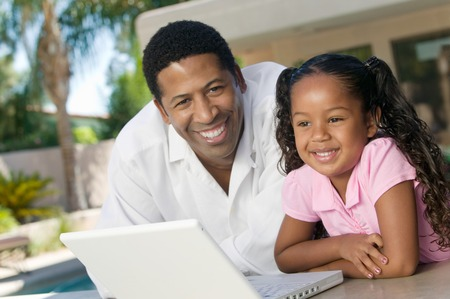 paternity: Father and Daughter Using Laptop
