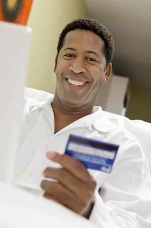 early 30s: Man Using Credit Card to Make Purchase with Laptop LANG_EVOIMAGES