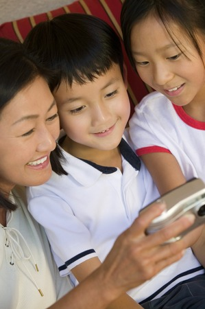 Mother and Children Looking at Digital Camera Stock Photo - 5419998