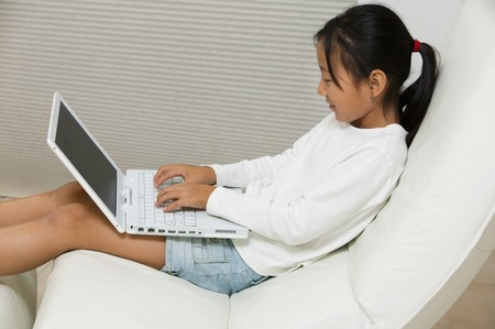 Young Girl in Chair Using Laptop Stock Photo - 5420005