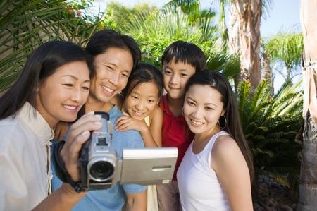 Family Looking at Video Camera Screen Stock Photo - 5420010