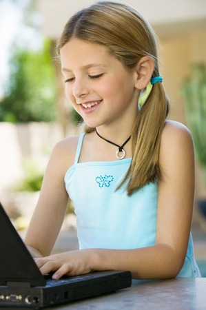 Girl Using Laptop on Outdoor Patio Stock Photo - 5420021