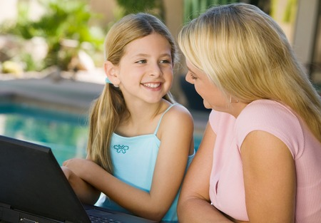 hooked up: Mother and Daughter Using Laptop on Patio