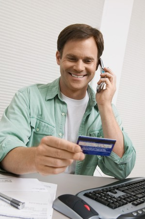 buy time: Man Using Credit Card to Order Over Phone LANG_EVOIMAGES