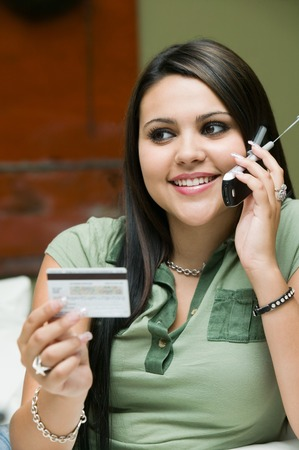 Woman Placing Credit Card Purchase on Cell Phone Stock Photo - 5428279
