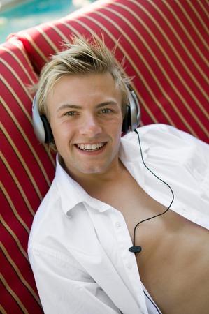 Man Listening to Music Poolside Stock Photo - 5428287