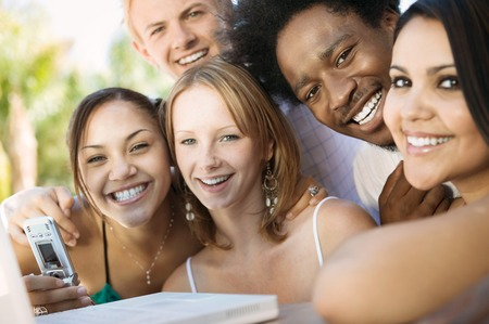 racially diverse: Friends Using Cell Phone and Laptop