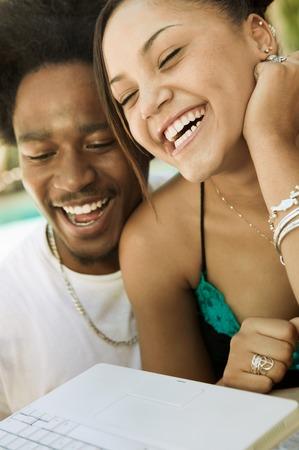 Laughing Couple Using Laptop Stock Photo - 5428300