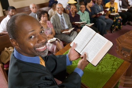 predicatore: Predicatore Holding Bibbia di fronte Congregazione