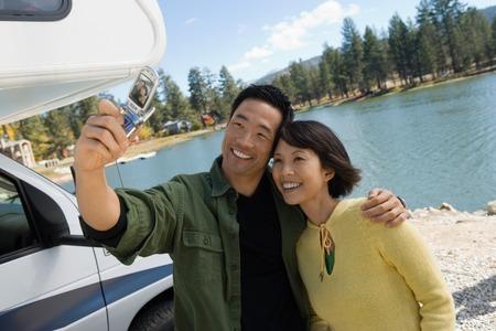 personas tomando agua: Pareja con c�mara de tel�fonos m�viles en el lago