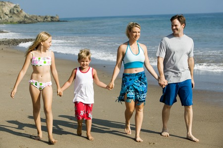 preadolescent: Family Holding Hands on Beach LANG_EVOIMAGES