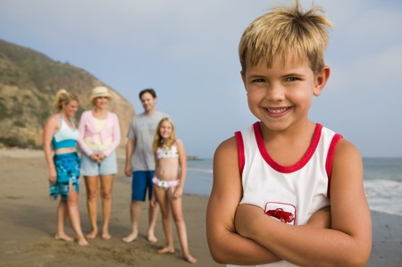preteens beach: Boy at Beach with His Family in Background