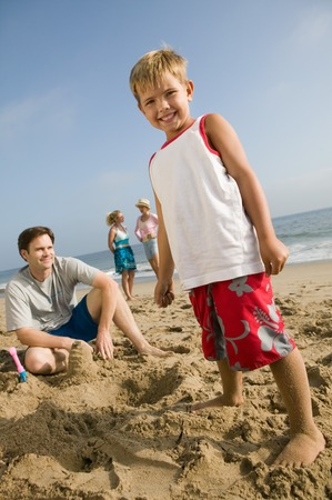 late summer: Boy Playing in Sand with Family at Beach LANG_EVOIMAGES
