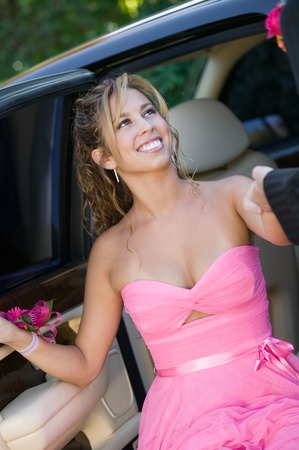 escort: Girl Dressed for Prom Being Helped from Limo LANG_EVOIMAGES